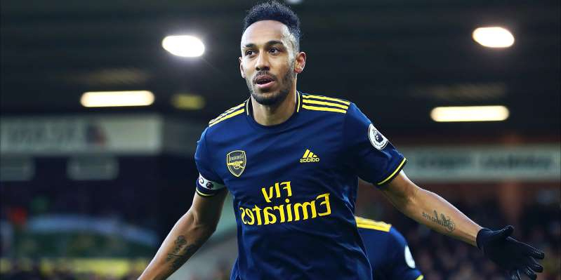 Pierre-Emerick Aubameyang wearing a blue uniform holding a ball: Football Gossip - Daily Round-Up