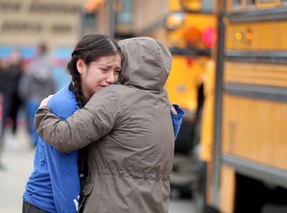 Slide 1 of 30: Gabriela Mauricio, 14, right, a freshman, hugs her mother Meche Mauricio, after the two were reunited outside Waukesha South High School in Waukesha on Monday, Dec. 2, 2019. Gunshots were exchanged between a student and a school resource officer inside Waukesha South High School, according to school officials.