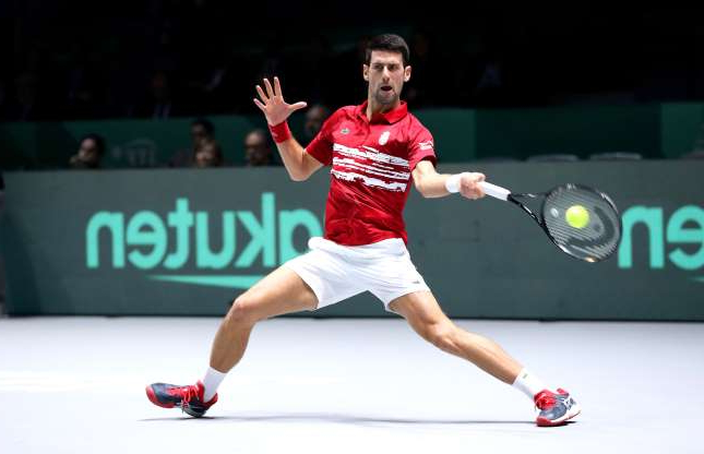 Slide 12 of 50: MADRID, SPAIN - NOVEMBER 20: Novak Djokovic of Serbia plays a forehand shot during his Davis Cup group stage match against Yoshihito Nishioka of Japan during Day Three of the 2019 Davis Cup at La Caja Magica on November 20, 2019 in Madrid, Spain. (Photo by Alex Pantling/Getty Images)