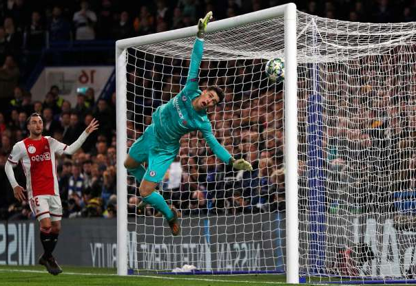 Slide 13 of 50: Chelsea's Spanish goalkeeper Kepa Arrizabalaga (C) dives but the ball hits the post and subsequently hits him for Ajax's third goal during the UEFA Champion's League Group H football match between Chelsea and Ajax at Stamford Bridge in London on November 5, 2019. (Photo by Adrian DENNIS / AFP) (Photo by ADRIAN DENNIS/AFP via Getty Images)