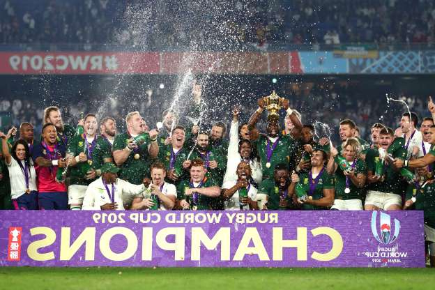 Slide 17 of 50: YOKOHAMA, JAPAN - NOVEMBER 02: Players of South Africa celebrate as Siya Kolisi of South Africa lifts the Web Ellis Cup following their victory against England in the Rugby World Cup 2019 Final between England and South Africa at International Stadium Yokohama on November 02, 2019 in Yokohama, Kanagawa, Japan. (Photo by Clive Rose - World Rugby/World Rugby via Getty Images)