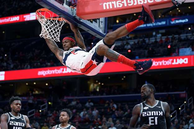 Slide 3 of 50: Washington Wizards guard Bradley Beal (3) hangs on the rim after his dunk above Sacramento Kings center Dewayne Dedmon (13), guard Yogi Ferrell, bottom center, and guard Buddy Hield, bottom right, during the second half of an NBA basketball game Sunday, Nov. 24, 2019, in Washington. The Kings won 113-106. (AP Photo/Nick Wass)