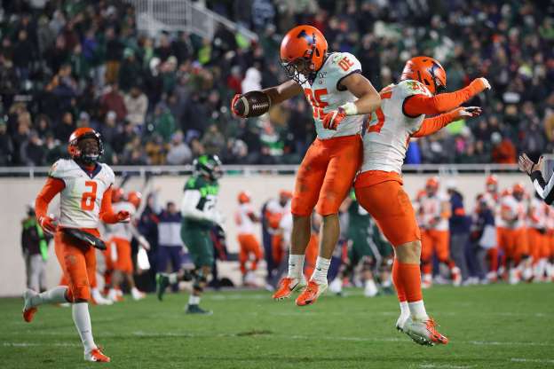 Slide 37 of 50: EAST LANSING, MICHIGAN - NOVEMBER 09: Sydney Brown #30 of the Illinois Fighting Illini celebrates his fourth quarter interception for a touchdown with Dawson DeGroot #24 while playing the Michigan State Spartans at Spartan Stadium on November 09, 2019 in East Lansing, Michigan. (Photo by Gregory Shamus/Getty Images)