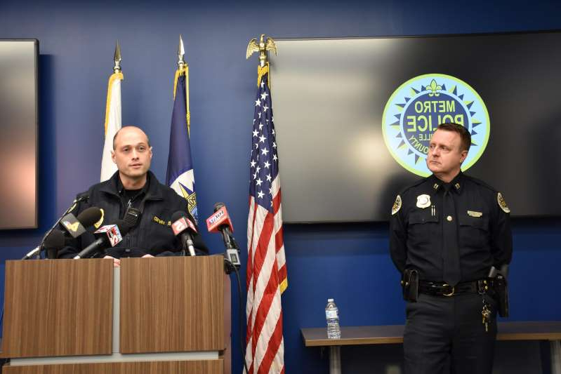 a couple of people that are standing in front of a stage: Metro Nashville Police officers Capt. Charles Widener, left, and Lt. Blaine Whited give an update on the search for four escaped juveniles accused of violent crimes at a news conference at MNPD headquarters on Monday, Dec. 2, 2019, in Nashville.