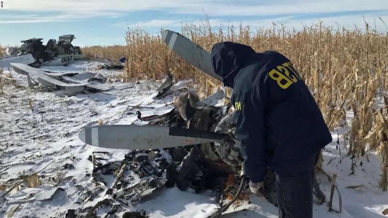 a couple of people that are standing in the snow: Investigators arrived at the Chamberlain, South Dakota, crash site on Monday, December 2, 2019.