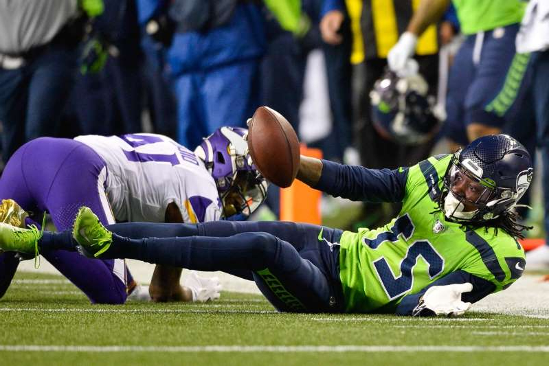 a football player kicking a ball: Seattle Seahawks cornerback Tre Flowers (21) intercepts a pass intended for Minnesota Vikings wide receiver Stefon Diggs (14) during the second half at CenturyLink Field. Seattle defeated Minnesota 37-30.