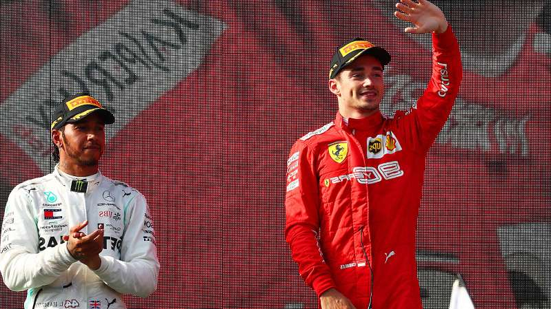 a group of baseball players standing on top of a field: Charles Leclerc of Monaco and Ferrari is applauded by third placed Lewis Hamilton