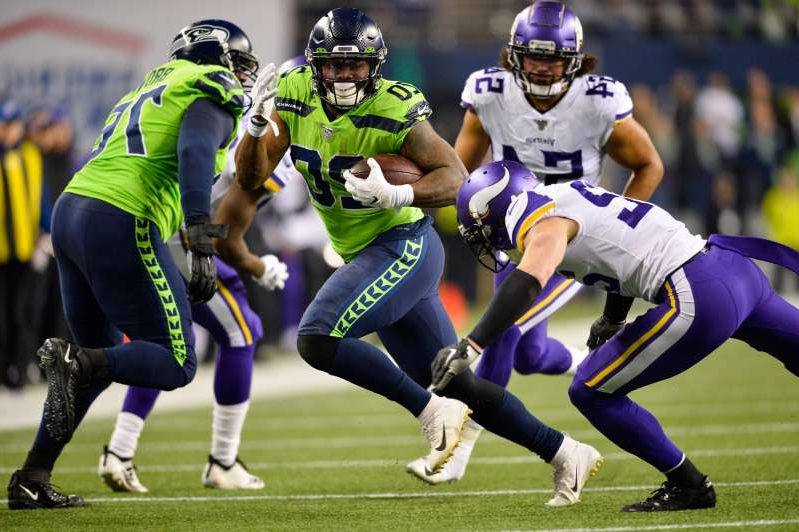 a group of football players playing a football game: Seattle Seahawks running back Rashaad Penny (20) carries the ball against the Minnesota Vikings during the first half at CenturyLink Field.