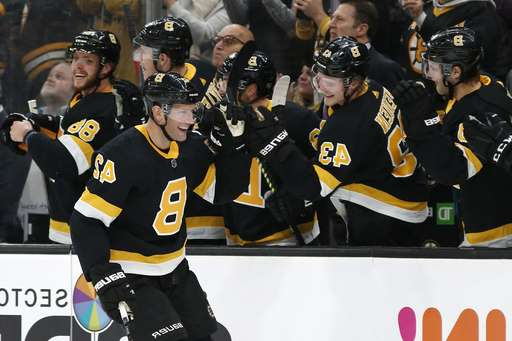 a group of people in uniform: Boston Bruins' David Backes is congratulated by teammates at the bench after scoring against the Montreal Canadiens during the third period of an NHL hockey game Sunday, Dec. 1, 2019, in Boston. (AP Photo/Winslow Townson)
