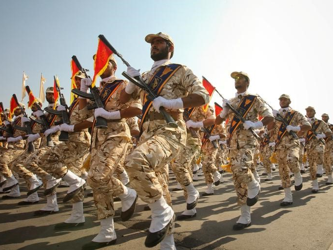 a group of people riding on the back of a horse: Members of the Iranian revolutionary guard march during a parade to commemorate the anniversary of the Iran-Iraq war (1980-88), in Tehran September 22, 2011.