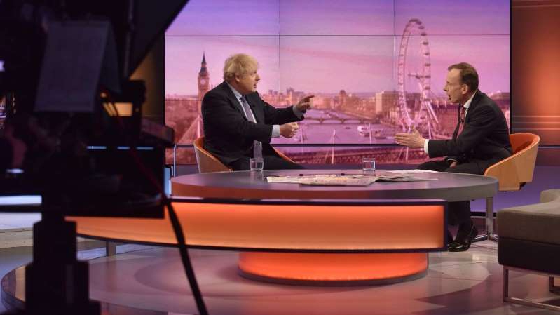a group of people sitting at a table in front of a laptop: Prime Minister Boris Johnson of Britain, right, during a segment of BBC's political program The Andrew Marr Show on Sunday.