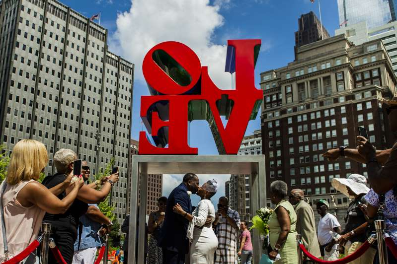 "a group of people standing in front of a building: Each month, 12 lucky couples can nab first-come, first-served time slots on ""Wedding Wednesdays."" They pay $50 for a 30-minute ceremony in front of Philly's iconic ""Love"" sculpture."