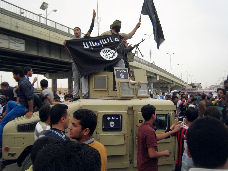 a group of people standing in front of a crowd: In this March 30, 2014 photo, Islamic State group militants hold up their flag as they patrol in a commandeered Iraqi military vehicle in Fallujah, Iraq.
