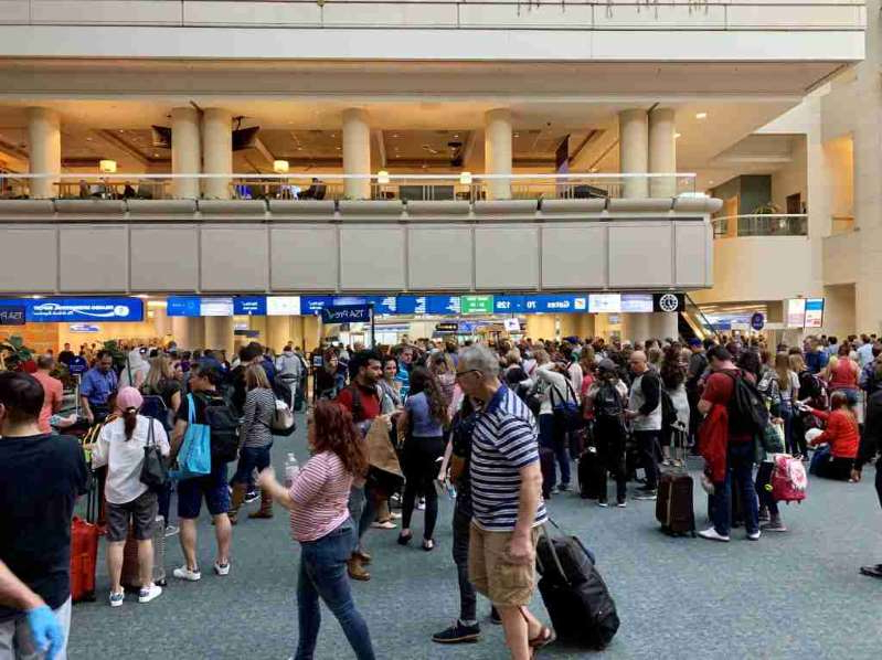 a group of people standing in front of a crowd: PreCheck can save you a ton of time when changing terminals. Photo by Summer Hull / The Points Guy