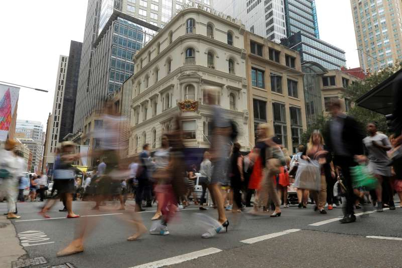 a group of people walking on a city street: Office workers walk the streets of Sydney, Australia