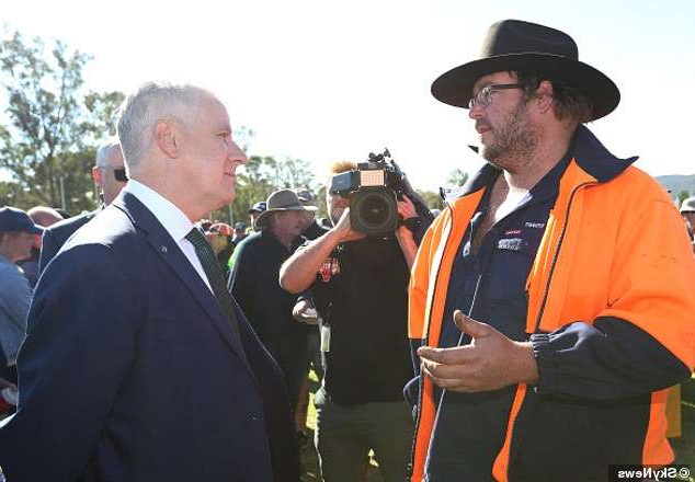 a man wearing a suit and tie talking on a cell phone: Mr McCormack (right) went out to meet the protesters when he was faced with furious farmers (left)