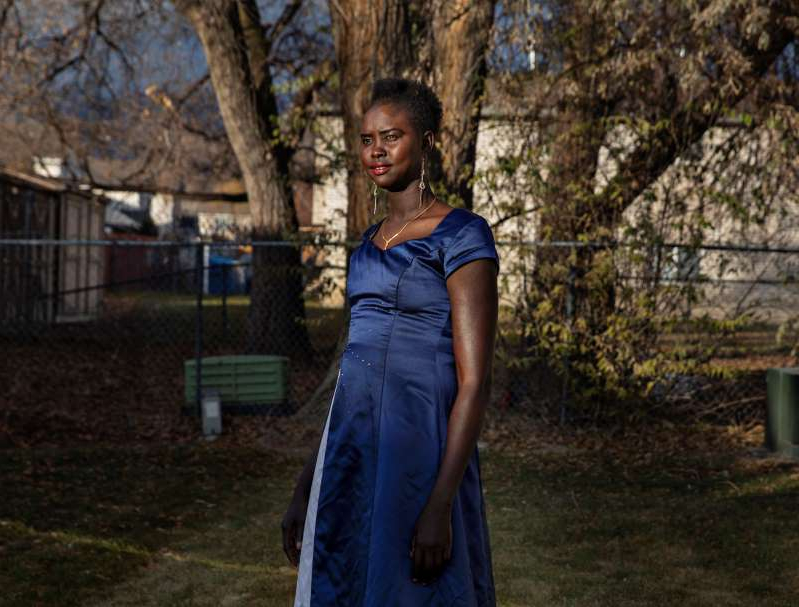 a person standing in front of a fence: Apiel Kuot, a 28-year-old refugee from present-day South Sudan, at her home in Midvale, Utah, last month.