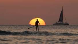 a sunset over a body of water: Photo of a person stand-up paddle boarding. They are silhouetted by the setting sun.