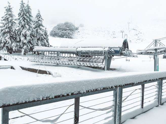 a train covered in snow: Falls Creek ski resort saw more than 20 cms fall this morning.