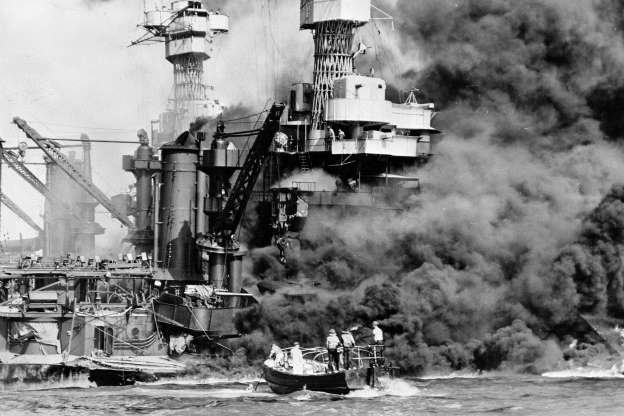 Folie 26 von 35: In this Dec. 7, 1941 photo made available by the U.S. Navy, a small boat rescues a seaman from the USS West Virginia burning in the foreground in Pearl Harbor, Hawaii, after Japanese aircraft attacked the military installation. More than 2,300 U.S. service members and civilians were killed in the strike which brought the United States into World War II.