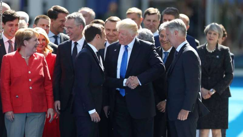 Raimonds Vējonis, Andrzej Duda standing in front of a crowd: Bloomberg Best of the Year 2017: U.S. President Donald Trump, center left, shakes hands with Emmanuel Macron, France's president, as other world leaders look on during a summit of world leaders at the North Atlantic Treaty Organization (NATO) in Brussels, Belgium, on Thursday, May 25, 2017. Photographer: Jasper Juinen/Bloomberg via Getty Images