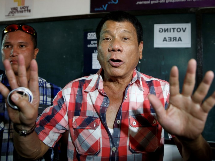 Rodrigo Duterte holding a pair of people posing for the camera: Then-presidential candidate Rodrigo 'Digong' Duterte talks to the media before casting his vote at a polling precinct for national elections at Daniel Aguinaldo National High School in Davao city in southern Philippines, May 9, 2016.