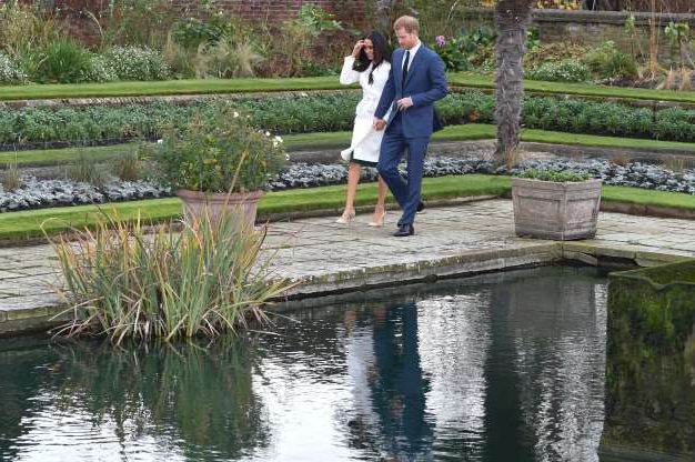 Slide 27 of 36: Britain's Prince Harry and his fiancée US actress Meghan Markle arrive to pose for photographs in the Sunken Garden at Kensington Palace in west London on November 27, 2017, following the announcement of their engagement. Britain's Prince Harry will marry his US actress girlfriend Meghan Markle early next year after the couple became engaged earlier this month, Clarence House announced on Monday. / AFP PHOTO / POOL / Eddie MULHOLLAND (Photo credit should read EDDIE MULHOLLAND/AFP/Getty Images)