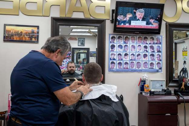 Slide 49 of 74: Barber John Enea, right, gives Kenneth Gary a hair cut as the public hearing of Donald Trump's impeachment investigation is shown on a television at the Expo Barber Shop in the Financial District of Manhattan, Nov. 13, 2019. The U.S. House launched the first public hearing Wednesday of Donald Trump's impeachment investigation, the extraordinary process to determine whether the 45th president of the United States should be removed from office.
