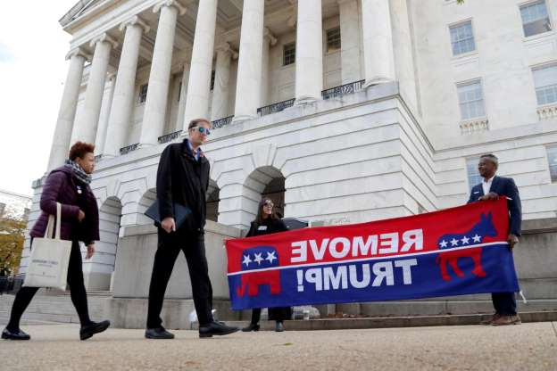 Slide 53 of 74: Pedestrians stroll by as demonstrator hold a sign outside Longworth House Office Building, where former U.S. Ambassador to Ukraine Marie Yovanovitch is testifying to the House Intelligence Committee, Nov. 15, 2019, on Capitol Hill in Washington, in the second public impeachment hearing of President Donald Trump's efforts to tie U.S. aid for Ukraine to investigations of his political opponents.