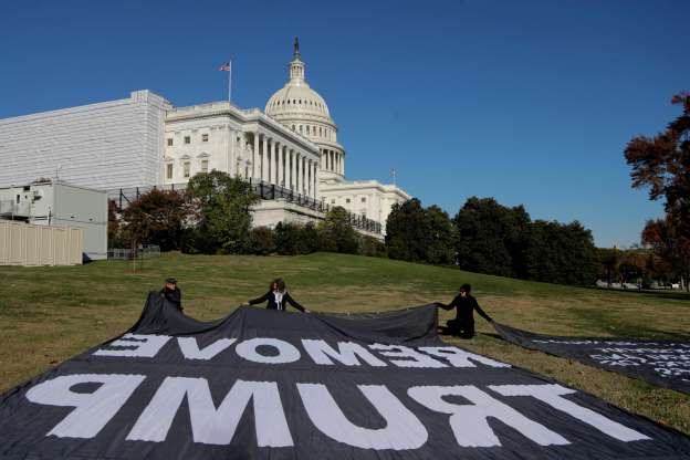 Slide 56 of 74: Demonstrators kneel near large banners on the lawn adjacent to the U.S. Capitol, while a top U.S. diplomat in Ukraine William Taylor, and career Foreign Service officer George Kent, testify before the House Intelligence Committee on Capitol Hill in Washington, Wednesday, Nov. 13, 2019, during the first public impeachment hearings of President Donald Trump's efforts to tie U.S. aid for Ukraine to investigations of his political opponents.