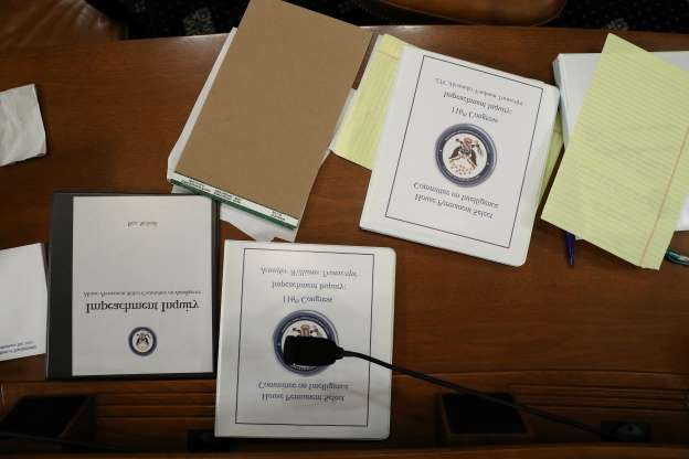 Slide 61 of 74: Briefing books related to the impeachment hearing are displayed as Lt. Col. Alexander Vindman (C), National Security Council Director for European Affair and Jennifer Williams, adviser to Vice President Mike Pence for European and Russian affairs, testify before the House Intelligence Committee in the Longworth House Office Building on Capitol Hill Nov. 19, 2019 in Washington, DC.  The committee heard testimony during the third day of open hearings in the impeachment inquiry against U.S. President Donald Trump, who House Democrats say withheld U.S. military aid for Ukraine in exchange for Ukrainian investigations of his political rivals.