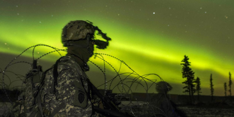 Soldiers secure an area in view of the aurora borealis during night live-fire training as part of Exercise Spartan Cerberus at Fort Greely, Alaska, October 25, 2016.