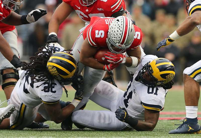 a group of baseball players on a field: Ohio State running back J.K. Dobbins dives past two Michigan defenders during their game in 2018 at Ohio Stadium.