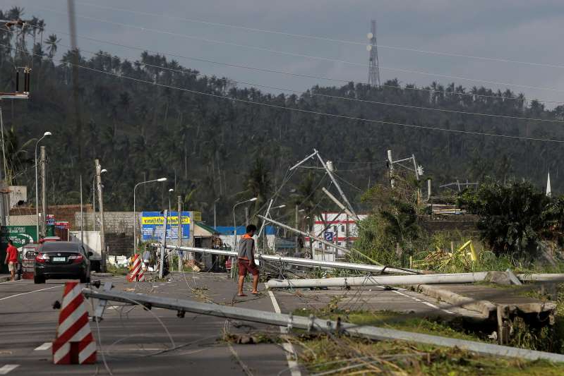 a group of people riding skis on a snowy road: A man walks past electric poles lying on the main highway after Typhoon Kammuri hit Camalig town