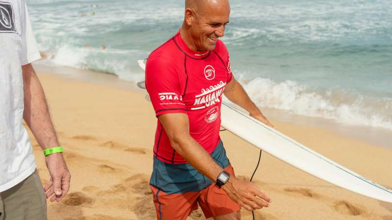 a man standing next to a body of water: Slater, 47, won his first world title the year Florence was born.