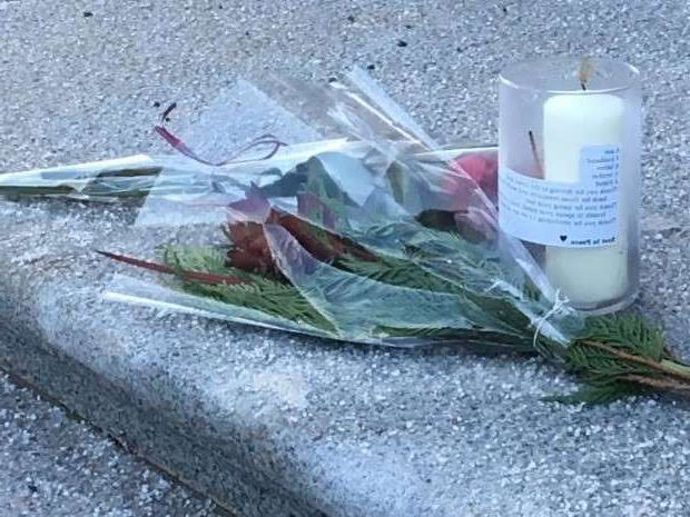 a plastic bag: A candle and flowers on the steps of the Alberta legislature, the spot where Ken Chan died by suicide Monday afternoon.