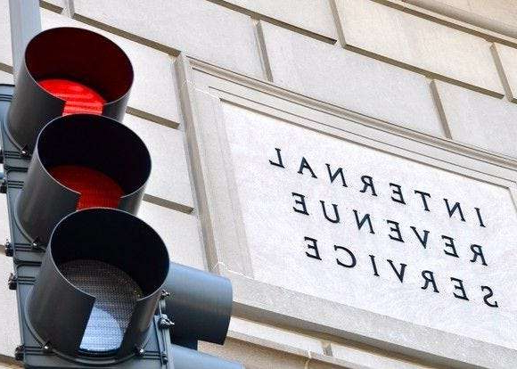 a stop light in front of a building: The Internal Revenue Service warns that crooks may try to use your bank account as part of a complicated scheme involving tax fraud.