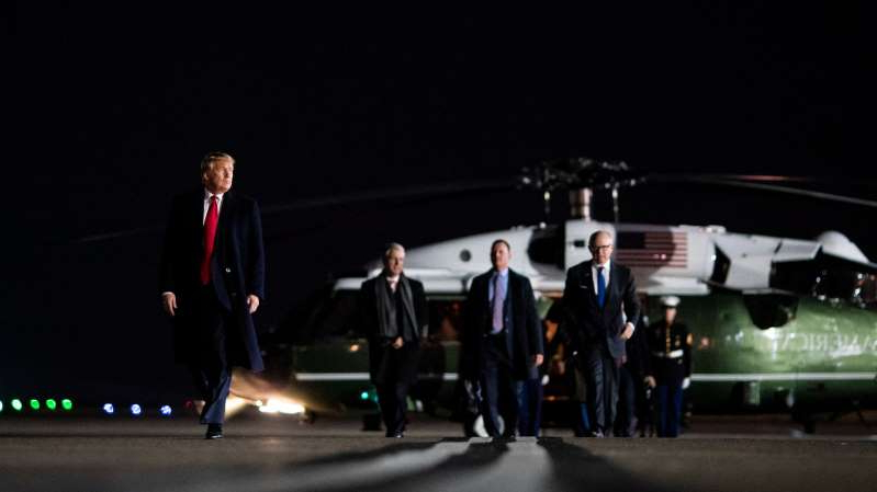 a group of people standing next to a man in a suit and tie: President Trump leaving London on Wednesday for Washington.