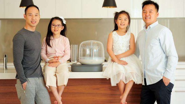 a person standing in front of a group of people posing for the camera: Alex and Ricky with their little girls and the Bottle Bath.