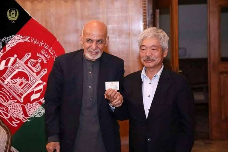 Ashraf Ghani in a suit standing in front of a building: Afghanistan's President Ashraf Ghani and Japanese doctor Tetsu Nakamura pose for a photo in Kabul
