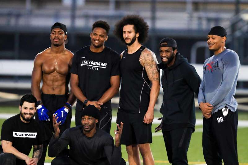 Colin Kaepernick, Brice Butler, Bruce Ellington posing for the camera: Colin Kaepernick stands with Bruce Ellington, Brice Butler, Jordan Veasy, and Ari Werts during the his workout at Charles R. Drew High School on Nov. 16 in Riverdale, Georgia.