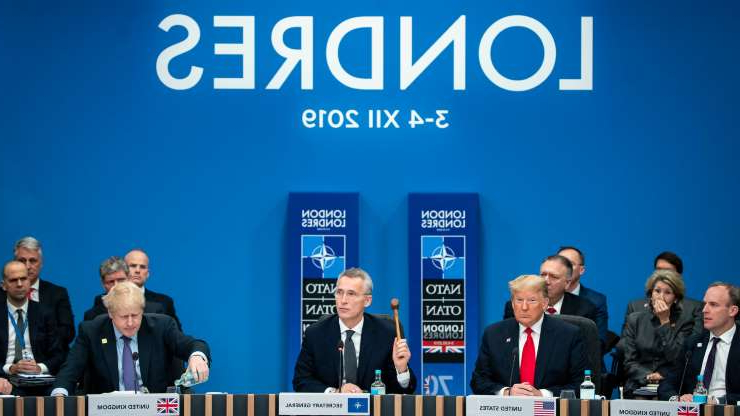 Dominic Raab, Donald Trump, Jens Stoltenberg, Boris Johnson standing in front of a sign: NATO Secretary General Jens Stoltenberg, center, during a NATO meeting on Wednesday.