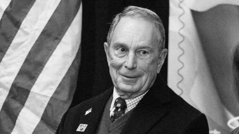 Michael Bloomberg wearing a suit and tie posing for a photo