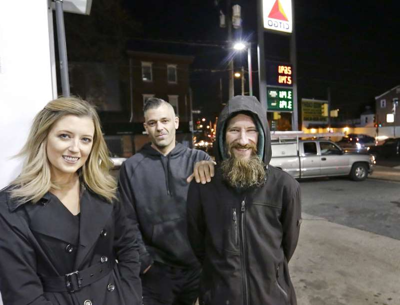 a couple of people posing for the camera: Johnny Bobbitt Jr., left, Kate McClure, right, and McClure's boyfriend Mark D'Amico