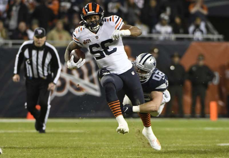 a football player on a field: Chicago Bears running back David Montgomery (32) runs with the ball as Dallas Cowboys outside linebacker Sean Lee (50) defends during the first half at Soldier Field.