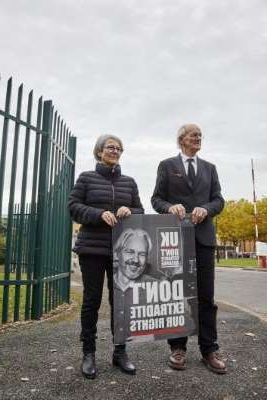 a man holding a sign posing for the camera: Assange's father John Shipton and former SBS newsreader Mary Kostakidis protest outside London's Belmarsh prison in October.