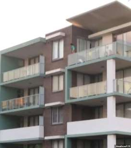 a tall building: A toddler has horrified onlookers after being seen perched perilously on the balcony ledge of a fourth-storey apartment