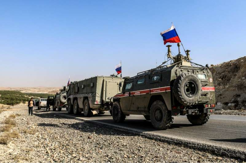a truck driving down a dirt road: ALEPPO, SYRIA - NOVEMBER 18: Russian soldiers, with Russian flag, are seen on armoured vehicle as they enter the base at the Tishrin Dam on the Euphrates, which the US troops' withdrew from, located 90 kilometres east of Aleppo in Aleppo Governorate, Syria on November 18, 2019. (Photo by Bekir Kasim/Anadolu Agency via Getty Images)