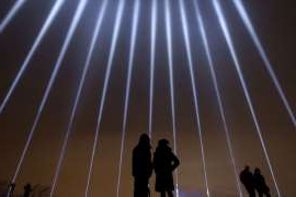 a group of people flying kites in the sky: A couple stands in silhouette against some of the 14 beams of light pointing skywards at the Mont Royal Chalet in commemoration of the 14 victims murdered at Polytechnique on Dec. 6, 1989.