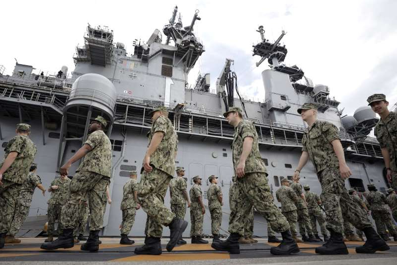 a group of people in military uniform standing in front of a building: U.S. military personnel gather to board the USS Wasp aircraft carrier ahead of the Memorial Day address by U.S. President Donald Trump at the U.S. naval base in Yokosuka, Kanagawa Prefecture, Japan, on Tuesday, May 28, 2019. Trump said talks with Japan focused on security and a trade deal between the allies are going well ahead of a meeting with U.S. troops stationed in the country, despite differences between the two sides that emerged earlier in the trip.